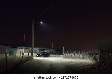 Lone car parked under a lamppost in the middle of the field at midnight