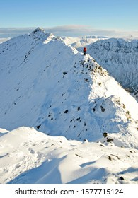 Lone climber on Striding Edge (Helvellyn, Lake District, England) on a perfect winter's day