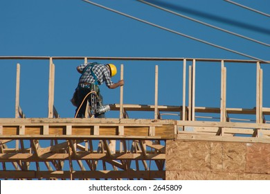 A lone construction worker on top of a new building with a nail gun strapped to his workbelt. No recognizable faces in image.
