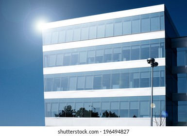 Lone, contemporary office building on a clear, blue day.