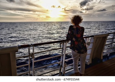 Lone Cruise ship Passenger Looking Out Over Ocean at Dusk