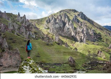 A lone female traveler standing on a rock spire in the shadows while thoughtfully looking out at strange rock formations in the mountains surrounding the city of Goris, Armenia