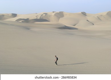 Lone figure in the desert with sand dunes.