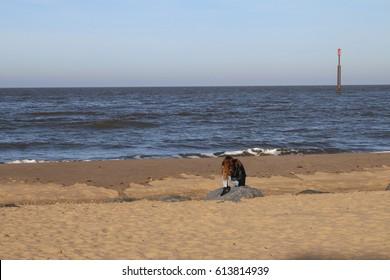 A lone figure like the lorelei statue of a mermaid kneeling on a deserted sandy Norfolk beach in England