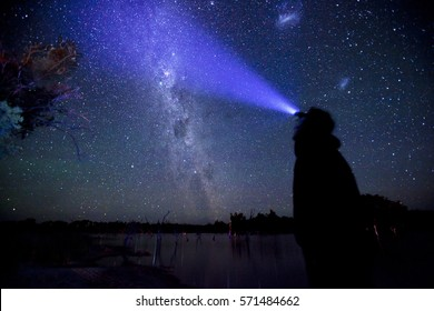 A lone figure looks out upon the milky way.
