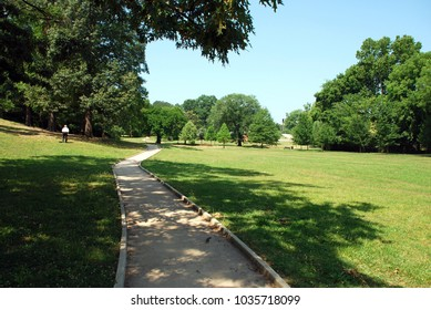 Lone figure in the sunny park