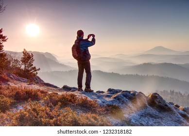 Lone figure watches the sunrise from sharp rock looking down at the wild landscape