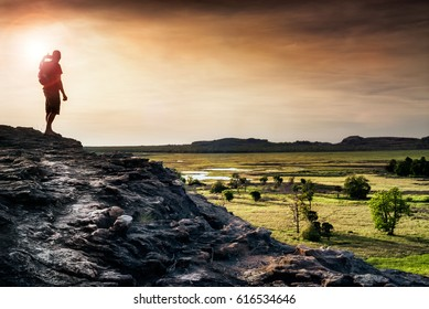 Lone figure watches the sunset from Ubirr rock looking down at the Nadab floodplains. Northern Territory, Australia