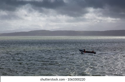 Lone fisherman heading out to sea on a stormy grey day