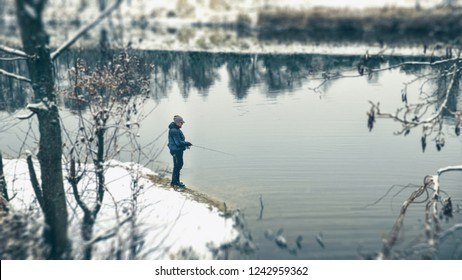 Lone fisherman on the bank of winter river.