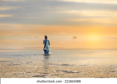 Lone fisherman on beach in the morning sunrise flare effect