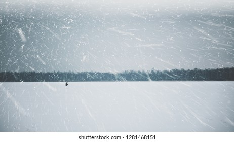A lone fisherman on a frozen lake. Ice fishing.
