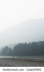 Lone fisherman on riverbank
