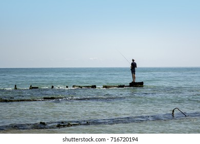 A lone fisherman in the sea is fishing.