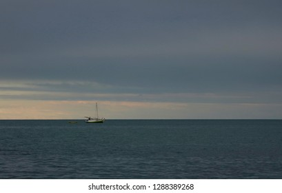 Lone fishing boat on the horizon of the Caribbean Sea in Hopkins, Belize at sunset