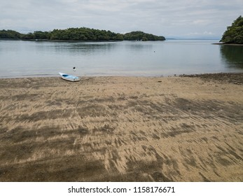 A lone fishing skiff sits on the low tide beach in Costa Rica