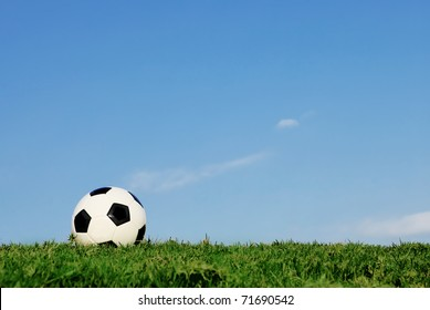 lone football on green football pitch of healthy strong grass