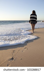 A lone girl walks out to the waterline on City beach, Perth, Western Australia
