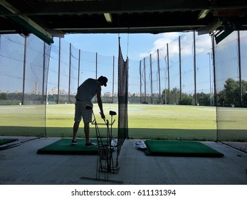 Lone golfer practicing his golf swing on driving range, view from behind