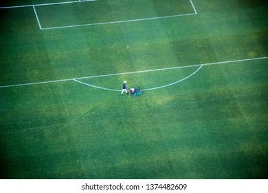Lone groundsman mowing soccer field