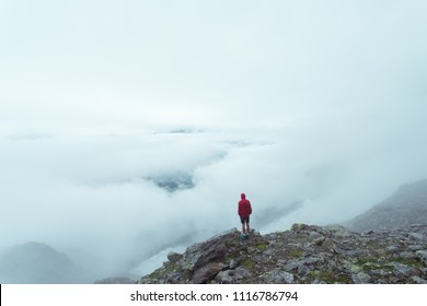 A lone hiker looking out over a valley filled with clouds in the Alps