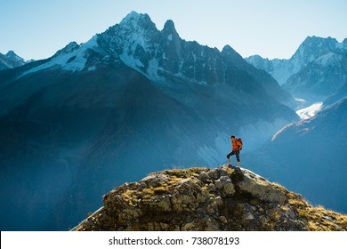 Lone hiker looking at the vast mountain landscape of snowy peaks while in the golden sunlight