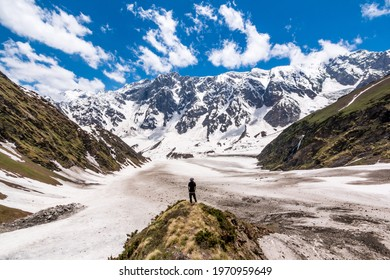 A lone hiker looks at the view of the Himalayas on the Beas Kund trek in northern India