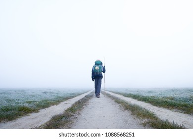 A Lone Hiker Walking off into the Frosty Morning Fog on the Camino de Santiago