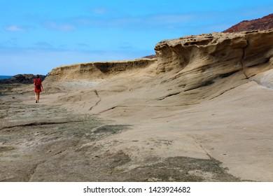 A lone hiker walks along arid petrified volcanic lava desolate landscape in El Medano, Tenerife
