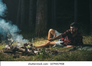 Lone hiker wandering in woods, camping concept.. Hipster cooking sausages over fire. Bearded barefoot man lying on grass.