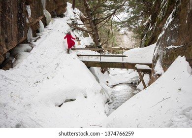 A lone hiker in winter walks along the edge of the trail in the Flume Gorge, Franconia Notch State Park, New Hampshire