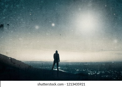 A lone hooded figure looking out across city lights before sunrise as mysterious light shine in the sky. With a vintage, grunge edit.