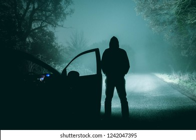 A lone, hooded figure standing next to a car looking at an empty misty winter country road silhouetted at night by car headlights. With a cold, grainy muted edit