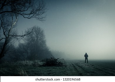 A lone hooded figure standing on a path on a spooky misty night, with a cold grainy blue edit.