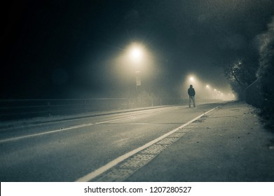A lone hooded man standing in the middle of a foggy road at night, with a grunge, vintage duo tone edit