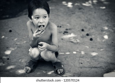Lone hungry boy eats sitting on the ground.