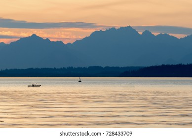 Lone kayak out on the water under the Olympic mountains at sunset near Seattle.