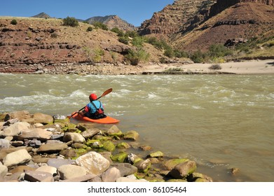 A lone kayaker paddling with canyon walls in the background.