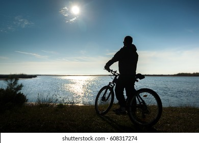 A lone man with bicycle relaxing in sunset sky at sea, river.