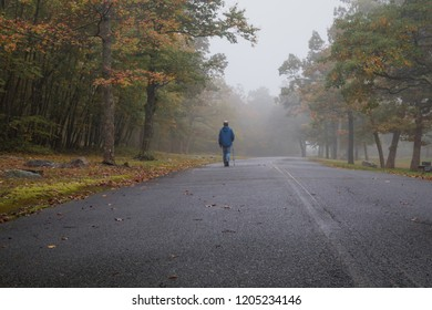 Lone man in blue jacket walks alone on a trail on a foggy morning in the fall