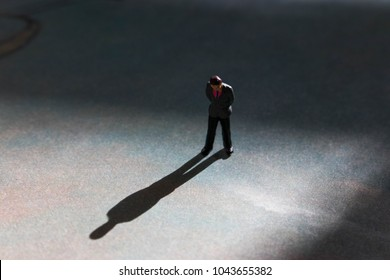 Lone man in empty space with dramatic shadow. Looking down at feet, he has a look of guilt or shame. Businessman guilty of white collar crime or dishonesty. Silhouette of unrecognizable shadow man.