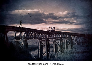Lone man and his dog wander across an abandoned wooden railway bridge through the countryside. Wandering soul, travelling man, road less travelled and mans best friend concepts