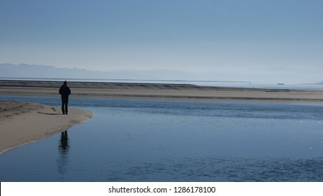 Lone Man on Beach by Estuary