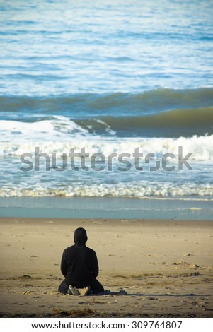 A lone man on sandy beach watching the ocean waves. Toned.