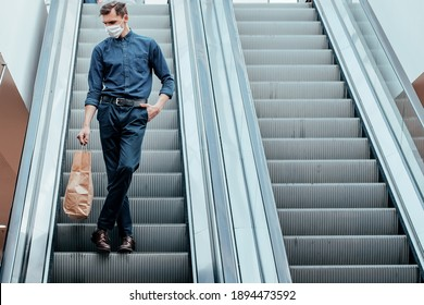 lone man in a protective mask standing on the escalator steps