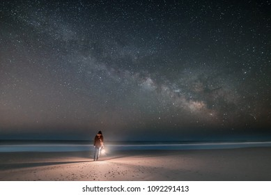 A lone man is seen on a beach under the Milky Way