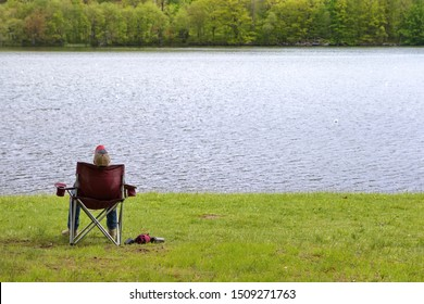 Lone man sleeping on a folding chair by the grassy shore of a river....Peace.