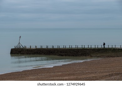 Lone man stands on the jetty on the coastline in Hove, Sussex, UK. Photographed in a cold winter's day.
