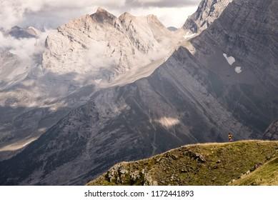 A lone man traverses a mountain ridge while trail running