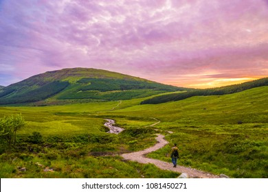 A lone man walking on the Fairy Pools trail in the Isle of Skye, Scotland, as the sun is setting.